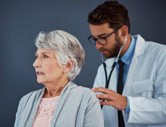 A doctor examining an old woman