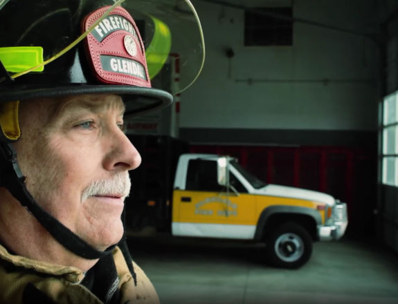 A firefighter man and a car in background