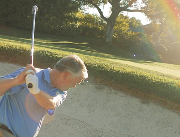A man swinging a golf club from a sandtrap