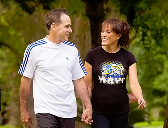 A man and a woman walking in a park holding hands and smiling while looking at each other