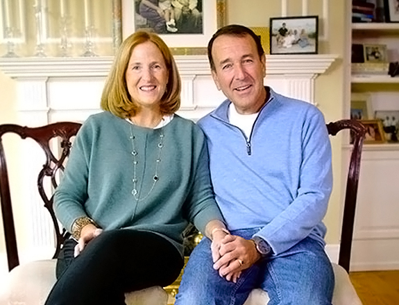 A man and a woman sitting in a living room and smiling at the camera